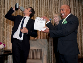 Ruffalo kisses the Renaissance Award while Walter holds up his proclamation