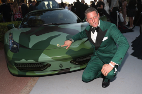Winner of cami Ferrari poses beside his new car