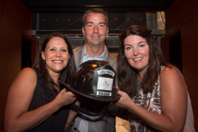 (L to R) WINGS in Chicago c-chairs Amy O'Keefe, Matt Baumann (board pres.) and Allison Szafranski pose with a fire helmet autographed by the cast of Chicago Fire for donation