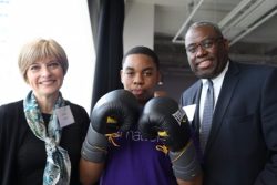 Kashim Skeete, ASM board member and Susan Baker meet a teen from the Art of Boxing program