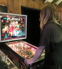 Aubree Connors playing her mom's pinball machine in game house.