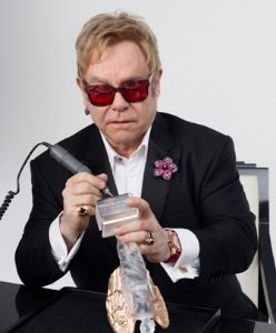 Elton John signs his name to a custom Lalique piece to benefit his Foundation