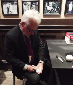 Cubs manager Joe Maddon signing baseballs for the raffle.