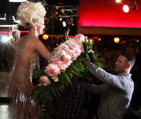 Derrick Taylor presents Mimi with a dramatic arrangement of flowers and dollar bills