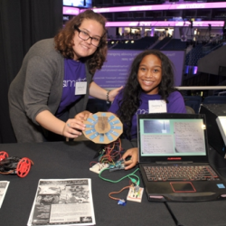 Teens Ashley and Destiny show off a circuit board they created in their summer program, powered by long-time youth program supporters ComEd