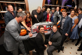 Dick Wolf cuts the Sugar Hills Bakery fire engine cake as cast members celebrate!