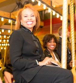 Cherie Richardson, Aux. Bd. member, takes a joyful spin on the Carousel.