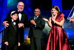 "Captain Lovell accepts the Lifetime Achievement Award with his ""biggest"" fan, Hudson Lindich (L)"