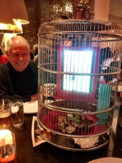 "Chuck admiring the creativity of the ""whole duck"" dish that was served in a bird cage"