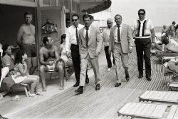 """Iconic image of """"Frank Sinatra – On the Boardwalk."""" Sinatra arrives at Miami Beach with his entourage (including his stand-in, dressed in an identical suit) while filming 'The Lady In Cement'. 1968. Photographer: Terry O'Neill"""
