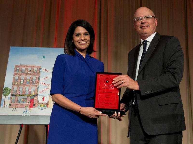 Board chair Tim Mohan presents Walgreen's award to Rina Shah.