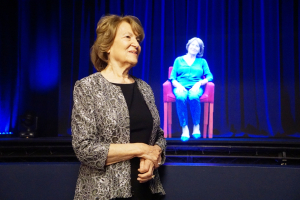 The late Fritzie Fritzshall in front of her hologram in Illinois Holocaust Museum's Survivor Stories exhibit.